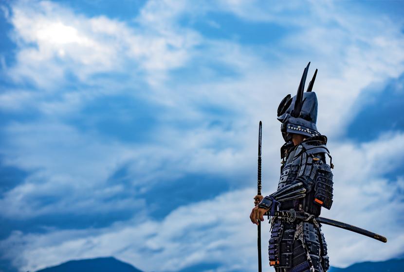 青空の下で佇む甲冑を着たサムライ