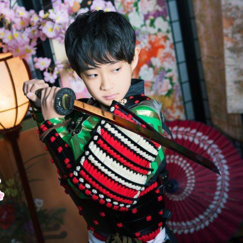 両手で刀を構える甲冑を着た子供武者